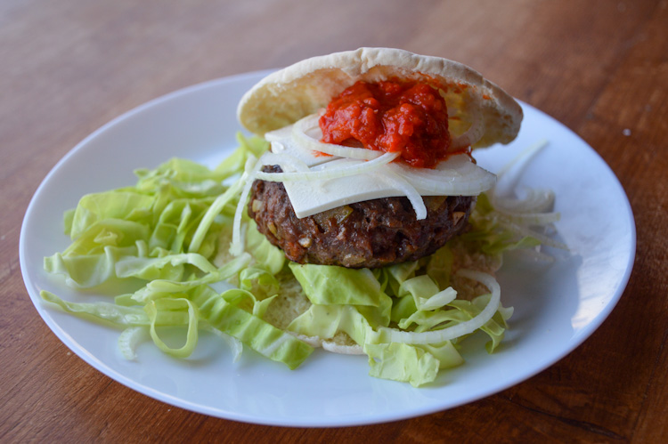 A Balkan burger, our version of pljeskavica inspired by cevapi, on a plate surrounded by green cabbage