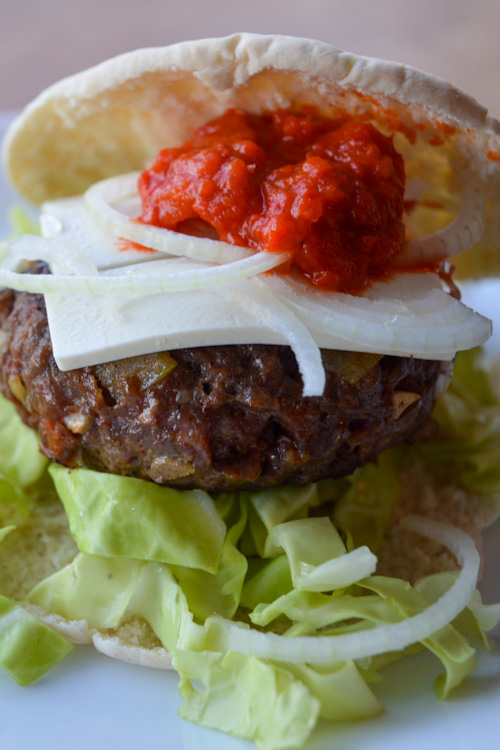 Close up of our Balkan burger with ajvar and white cheese on a pita