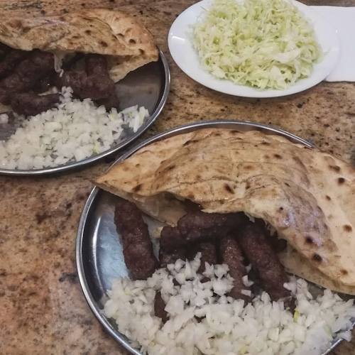 Two plates of cevapi plus one plate of cabbage in Sarajevo