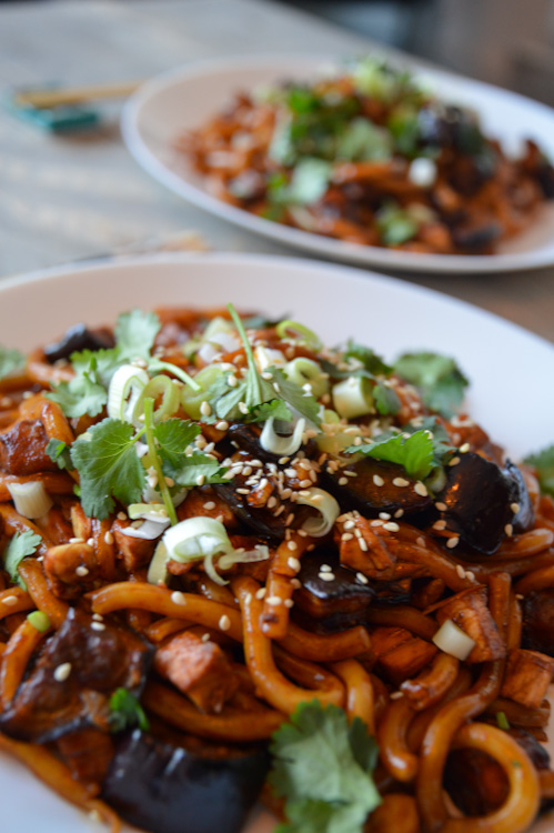 Close up of two plates of our take on yaki udon: udon noodles with miso roasted eggplant