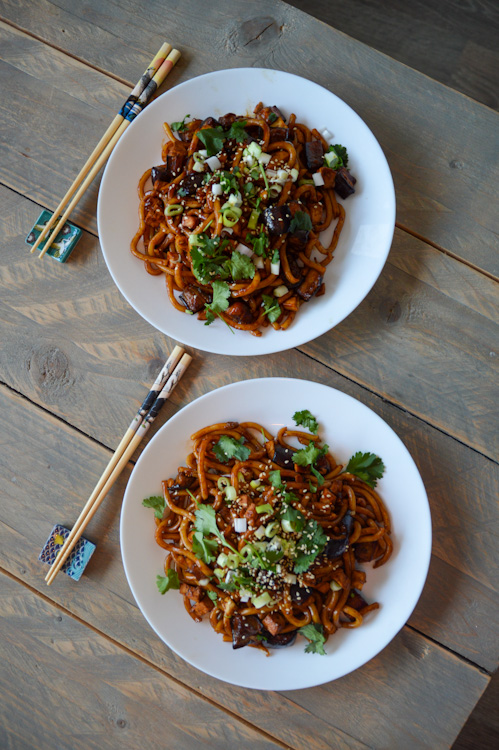 Two plates of udon noodles with miso roasted eggplants and chopsticks on a table