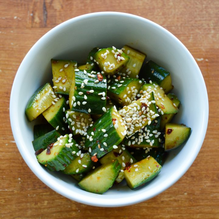 White bowl of Sichuan cucumber salad with sesame seeds