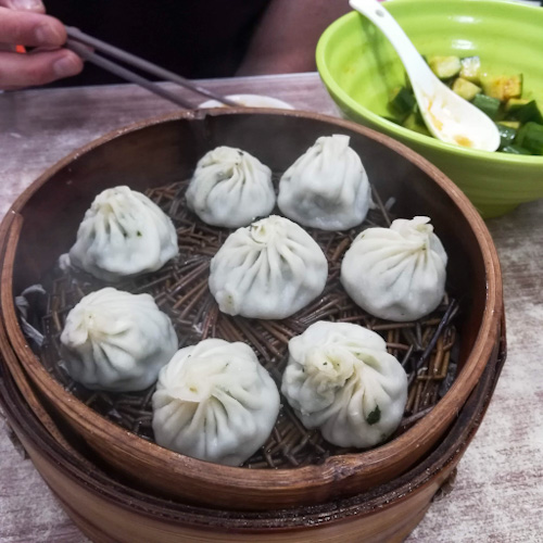 A basket of steamed soup dumplings and a green bowl of cucumber salad in Shanghai