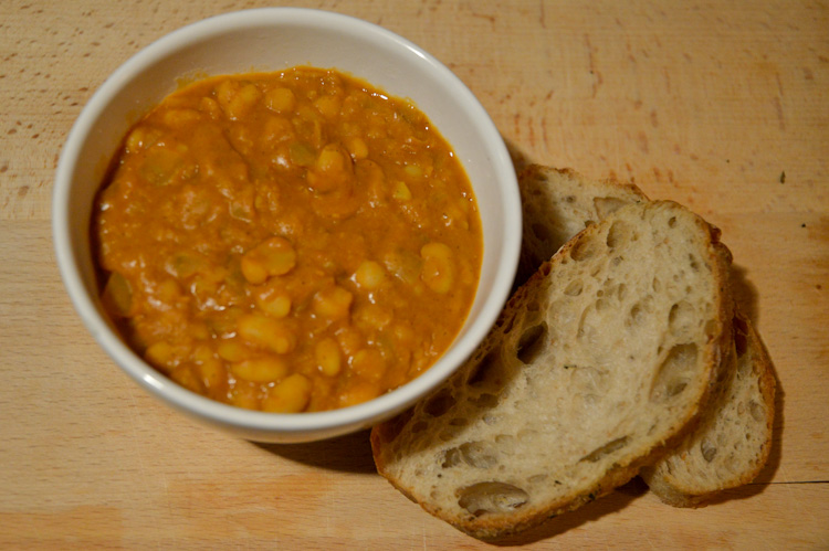A bowl of Macedonian beans with two pieces of bread next to it