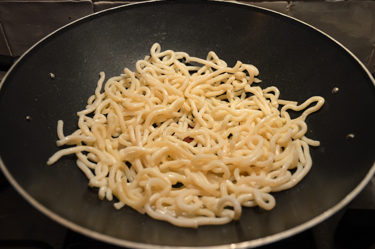 Udon noodles cooking in a wok