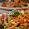 Two plates of veggie udon noodles, one in focus in front and another blurred in the back