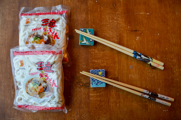 Two packages of udon noodles on a table next to two sets of chopsticks