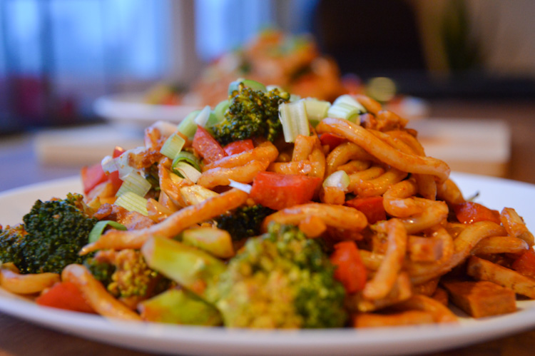 Close up of a plate of veggie udon noodles with broccoli and red pepper