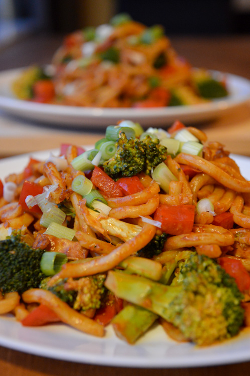 Two plates of veggie udon noodles with peanut sauce featuring broccoli, red pepper, and tofu