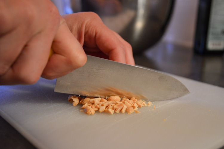 Hands chopping peanuts with a knife on a cutting board for Dutch peanut sauce