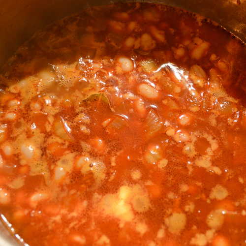 A red liquid with beans cooking in a pot