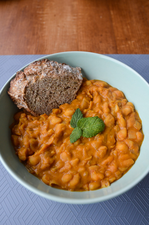 Tavce gravce inspired Macedonian beans in a bowl with a piece of crusty bread