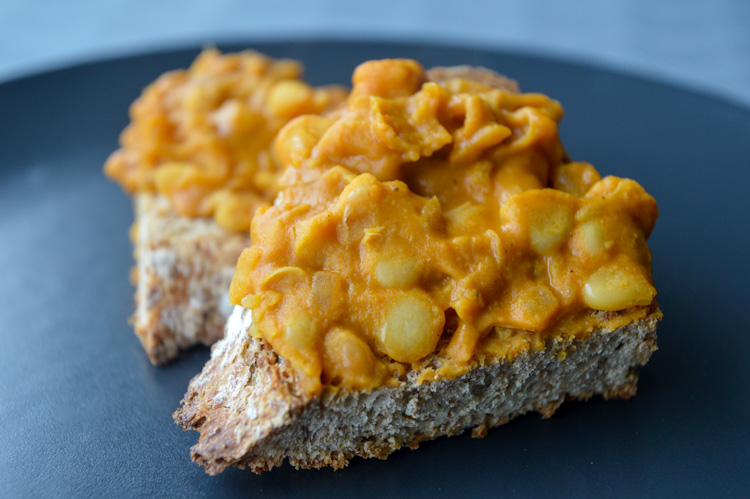 Macedonian beans (our version of tavce gravce made with canned beans) atop two pieces of crusty toast on a black plate