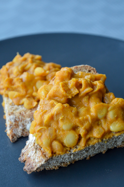 Orange colored mashed beans - our take on tavce gravce - on top of toasted crusty bread on a black plate