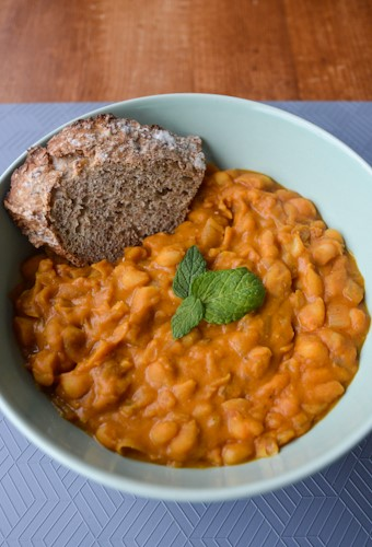 Light green bowl with deep orange tavce gravce inspired Macedonian beans with a piece of toasted bread