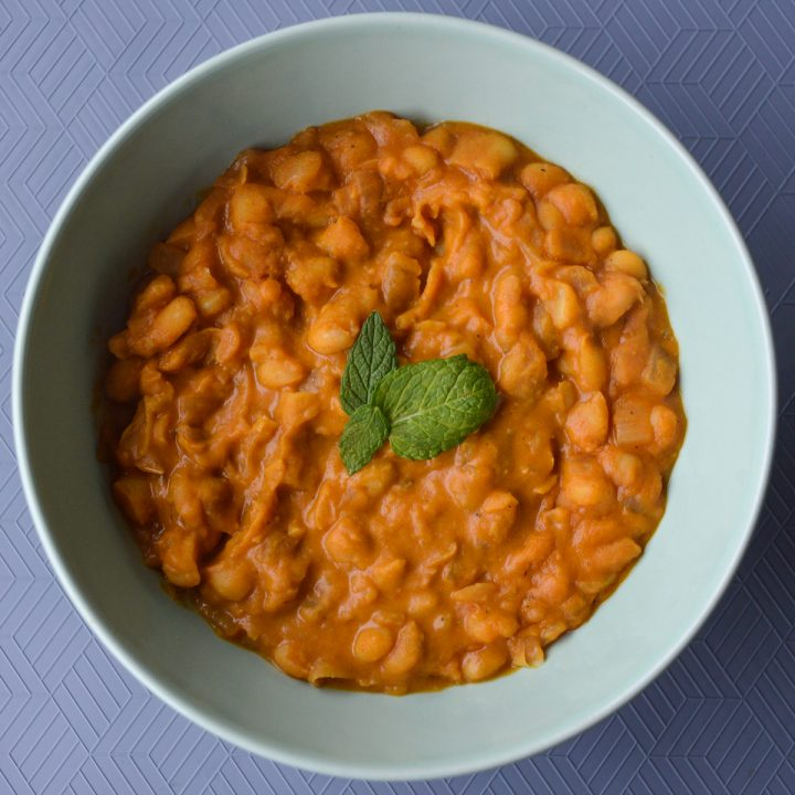 Tavce gravce inspired Macedonian beans - creamy orange colored beans in a bowl topped with a few mint leaves