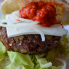 Super close up our Balkan burger showing toppings of feta cheese, raw onion, and ajvar