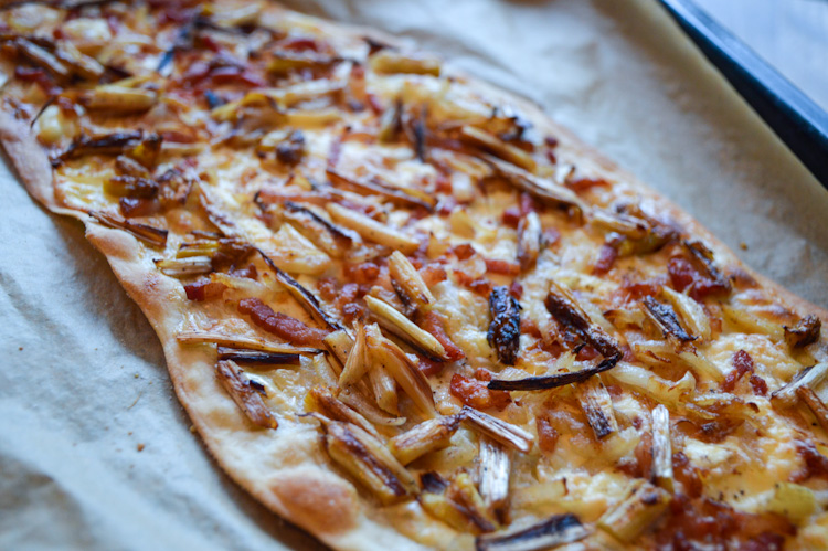 Flammkuchen with white asparagus on a baking sheet