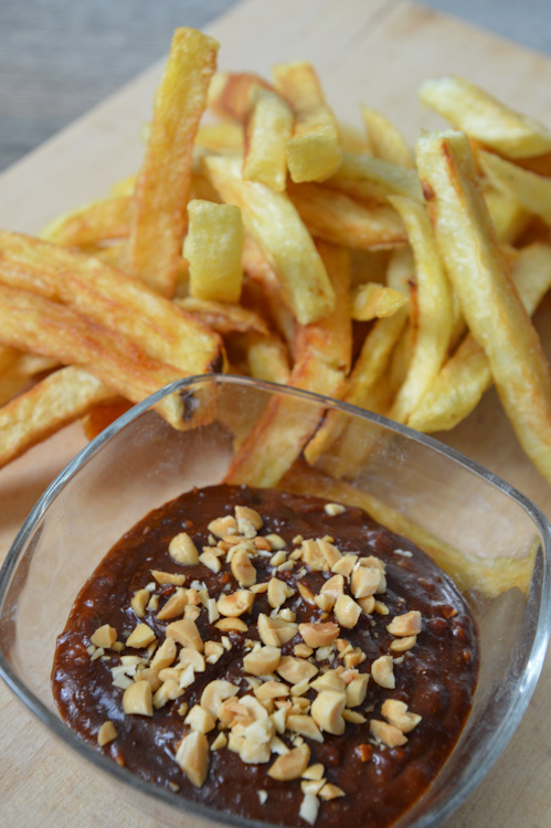 Close up of pindasaus (Dutch peanut sauce) with french fries on a wood board