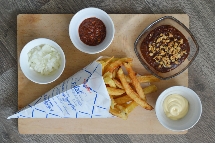 All the ingredients for patatje oorlog (Dutch war fries): fries, pindasaus, mayonnaise, raw onions, and sambal