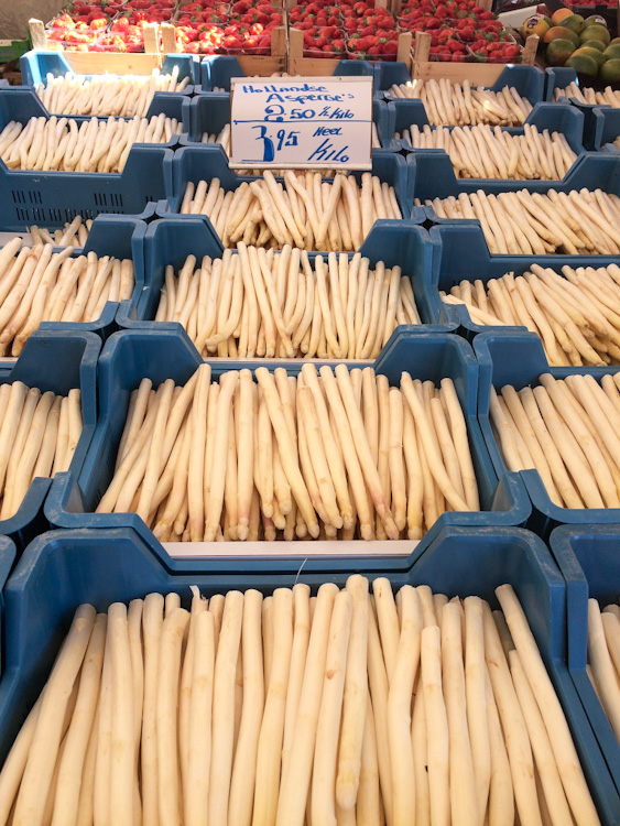 White asparagus in blue bins at an outdoor market