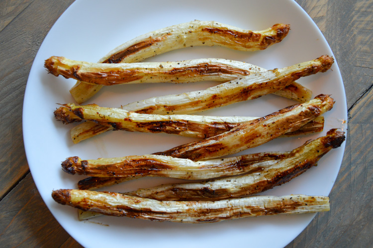 8 roasted white asparagus on a white plate