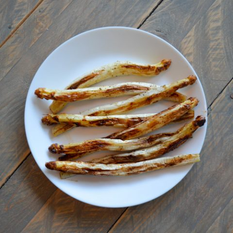 Roasted white asparagus served on a white plate