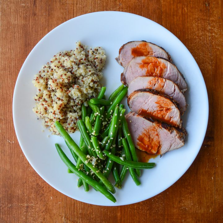 Thai grilled pork tenderloin sliced and sauced, on a plate with quinoa and green beans