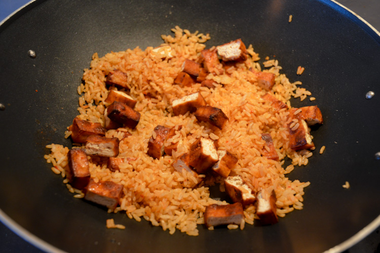 Brown rice and pieces of tofu cooking in a wok