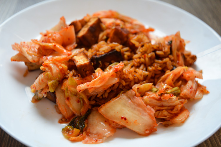 Close up of gochujang fried rice with kimchi and tofu on a white plate