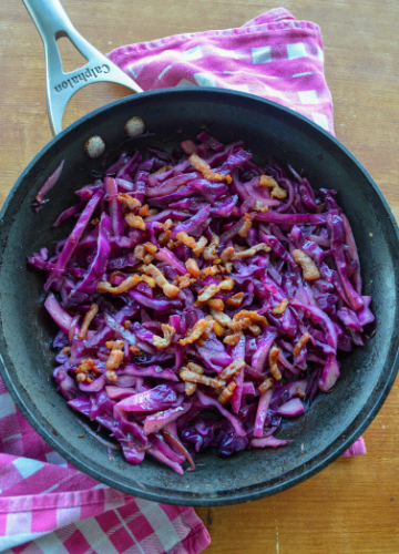 Sautéed red cabbage with crispy bacon lardons on a pink and white towel