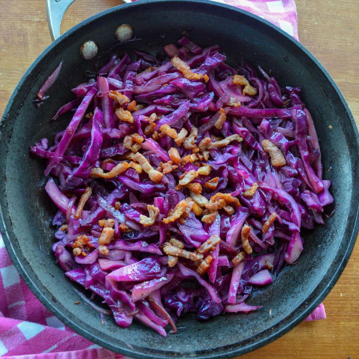 Square picture of sautéed red cabbage topped with bacon lardons in a pan