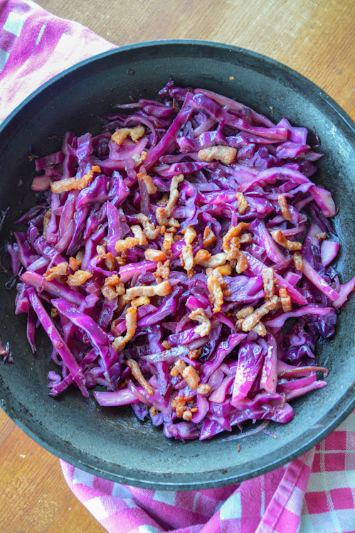 Sautéed red cabbage with bacon on a pink and white towel