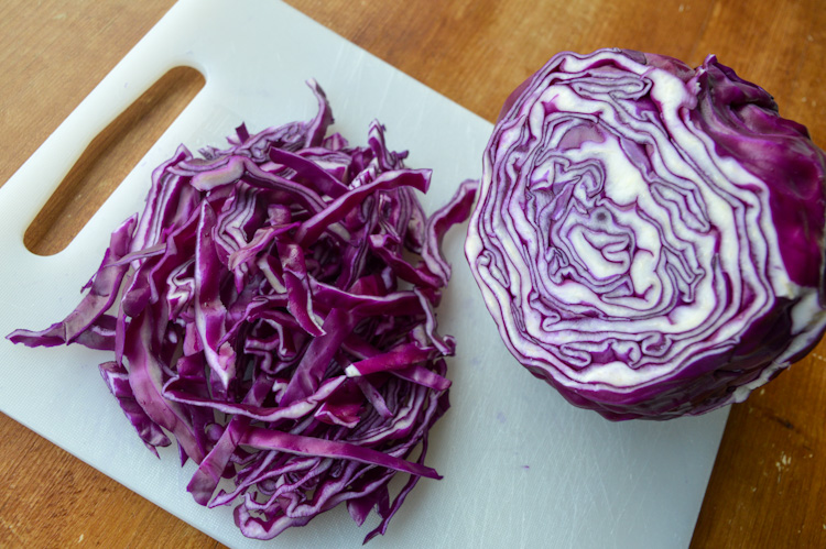 Half a red cabbage and half a cabbage chopped on a white cutting board