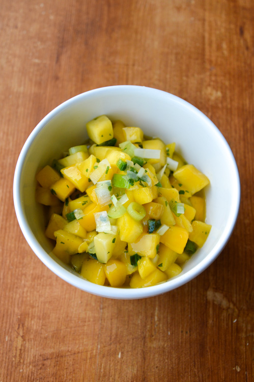 Mango jalapeño salsa in a white bowl on a brown table