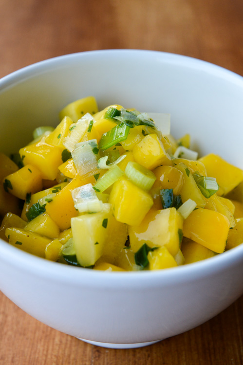 Close up of a white bowl of spicy mango salsa with a brown table background