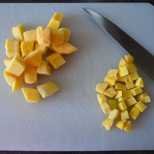 Frozen mango pieces chopped in different sizes