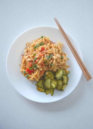 White plate of spicy peanut noodles with cucumber salad and chopsticks on a white background