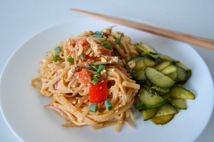 Angled view of a white plate of spicy peanut noodles with red peppers next to pickled cucumbers, with chopsticks