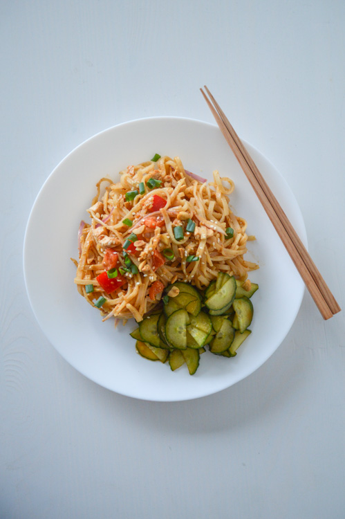 White plate with spicy peanut noodles, served cold, and a side of pickled cucumbers, seen with chopsticks