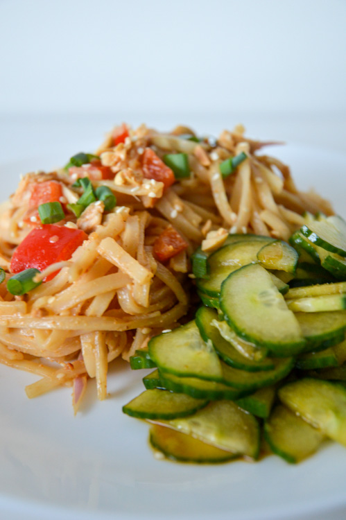 Close up of cold spicy sesame noodles with a side of cucumber salad, served on a white plate against a white background