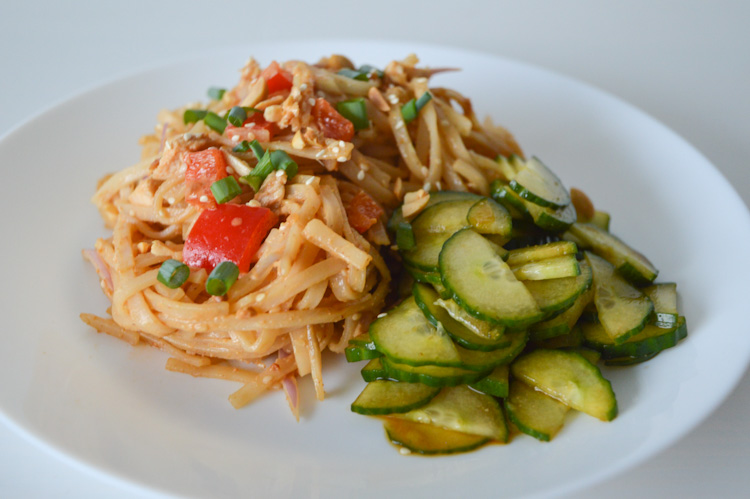 A white plate of cold noodles with red peppers, chicken, topped with a spicy peanut sauce served with cucumbers on the side