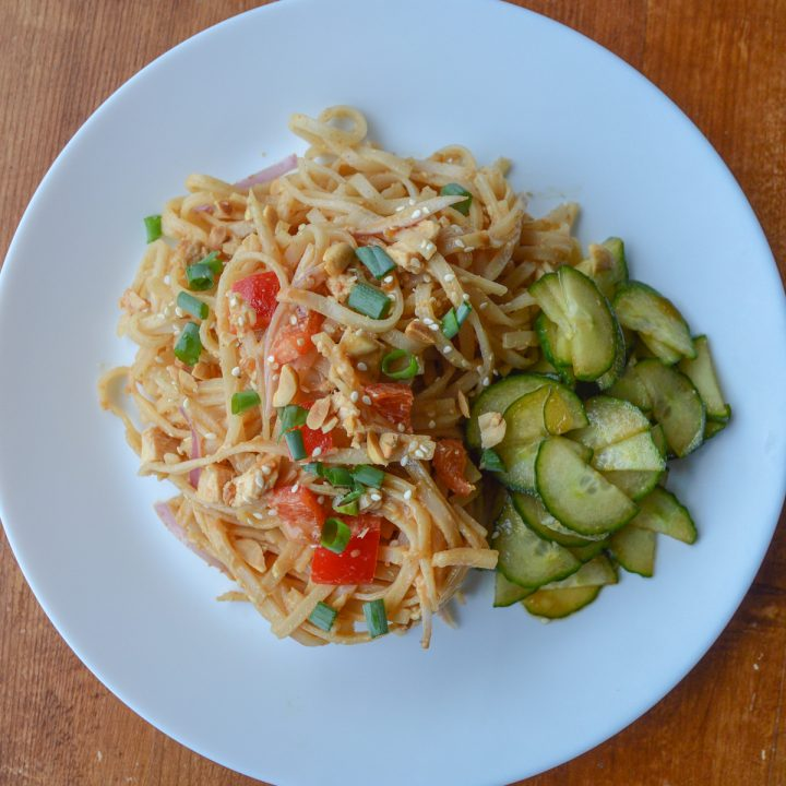 White plate of spicy peanut noodles, served cold, with cucumber salad