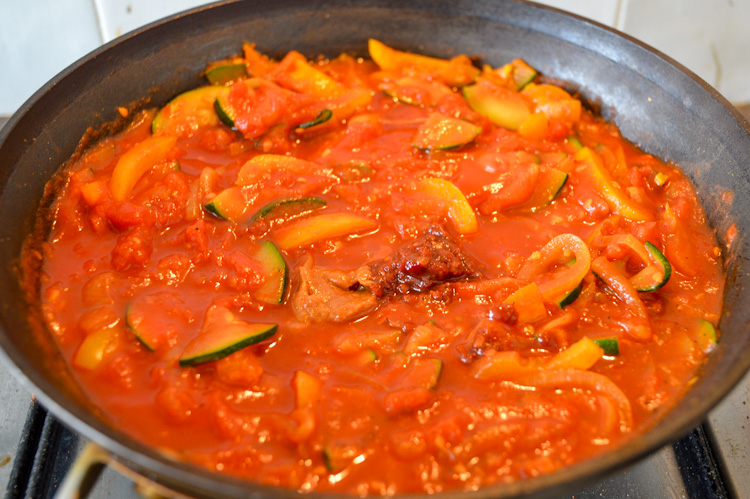Vegetables stewing in tomato sauce with dollops of miso paste and sambal on top