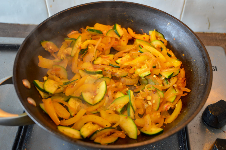 Vegetables sautéing in a skillet including yellow peppers and zucchini