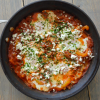 Shakshuka for two with feta and parsley in a skillet