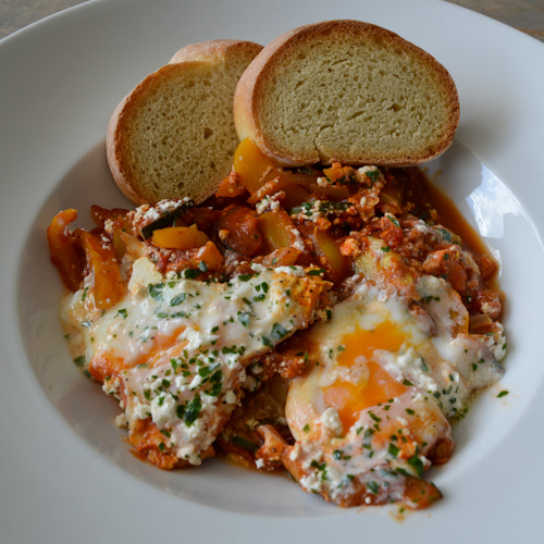 Shakshuka for two in a bowl with runny eggs and toasted bread