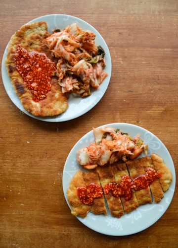Two plates of Korean tonkatsu with gochujang sauce served with sides of kimchi on a brown table