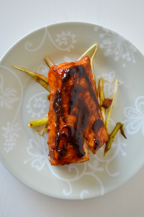 Top down view of one piece of baked cod fillet on a bed of julienned green onions; cod is topped with a miso ginger marinade glaze