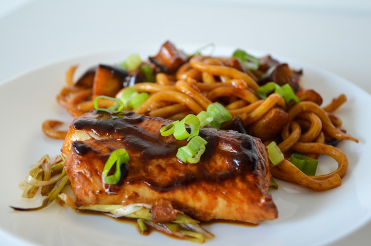 Side view of a plate of baked cod with miso ginger marinade and udon noodles topped with chopped green onions